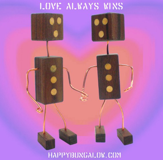 Two handcrafted wood robots holding hands with the caption, LOVE ALWAYS WINS