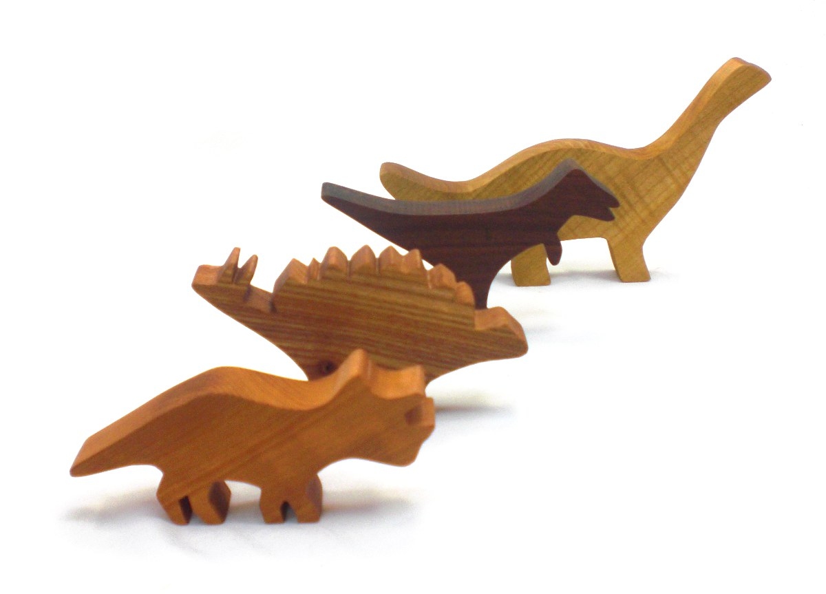 wood toy dinosaurs, t-rex, brontosaurus, stegosaurus, and triceratops